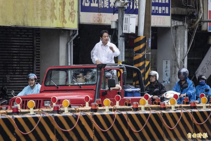 身穿白色襯衫的賴清德頭髮被大雨淋濕仍繼續向汽機車騎士和民眾揮手拜票。(記者邱書昱攝)