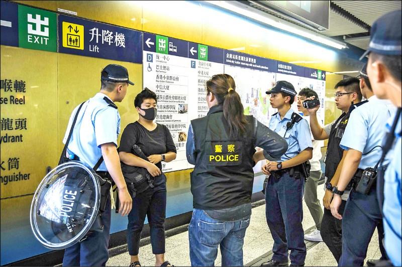 香港政府堅持修訂「逃犯條例」,大批香港民眾11日晚間冒雨聚集在立法會旁的公民廣場,港府調派5千名警力應對,晚間8時起全面配槍執勤,甚至搜查車輛及地鐵乘客。(法新社)