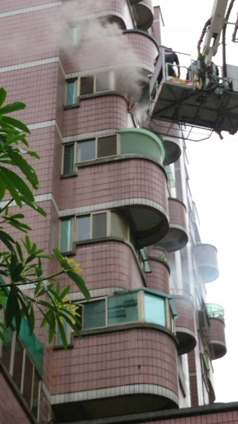大樓8樓不斷竄出濃煙,妙齡女雙腳騰空坐在陽台呼救。(消防局提供)