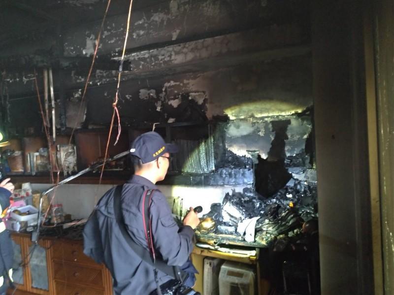 消防人員檢視火場,屋內客廳電視機旁的櫃子已遭燒毀。(消防局提供)