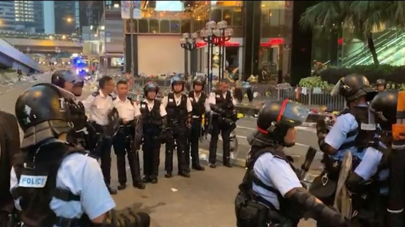 幾名香港警察面露微笑站成一排,有另名警員幫忙拍照留念。(圖擷自香港電台視像新聞 RTHK VNEWS 臉書)