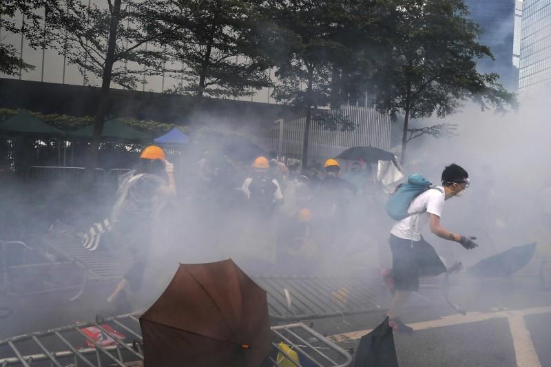警方施放催淚彈後,現場抗議者試圖奔逃遠離。(美聯社)