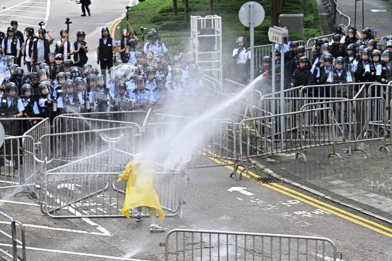 有民眾欲衝破警封鎖線,遭警方利用辣椒水與強力水柱驅散。(法新社)