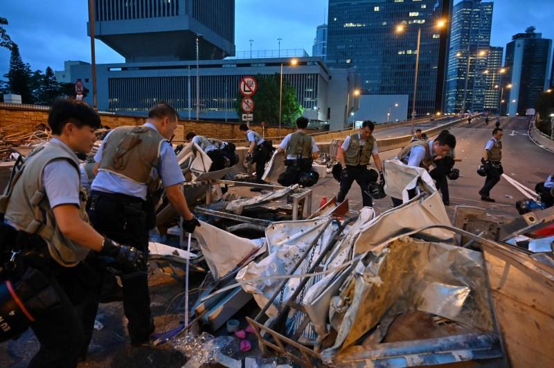 警方於今凌晨持續清理示威現場遺留的雜物。(法新社)