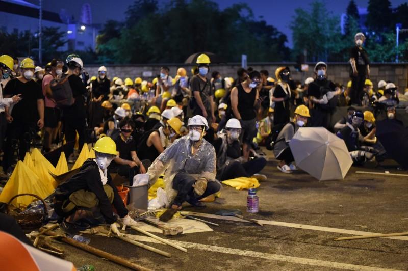 昨日下午在警方不斷施放催淚彈後,示威者陸續退到中環,截至今凌晨示威者開始離開干諾道中的防線,並勸留守者暫時離開現場。(法新社)