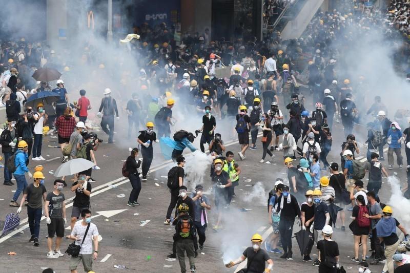 香港政府強推《逃犯條例》觸發612罷工罷課行動,大批抗議群眾在立法會示威區外聚集,下午爆發衝突傳出槍響,警方施放催淚彈、發射布袋彈等,現場一片混亂。(法新社)