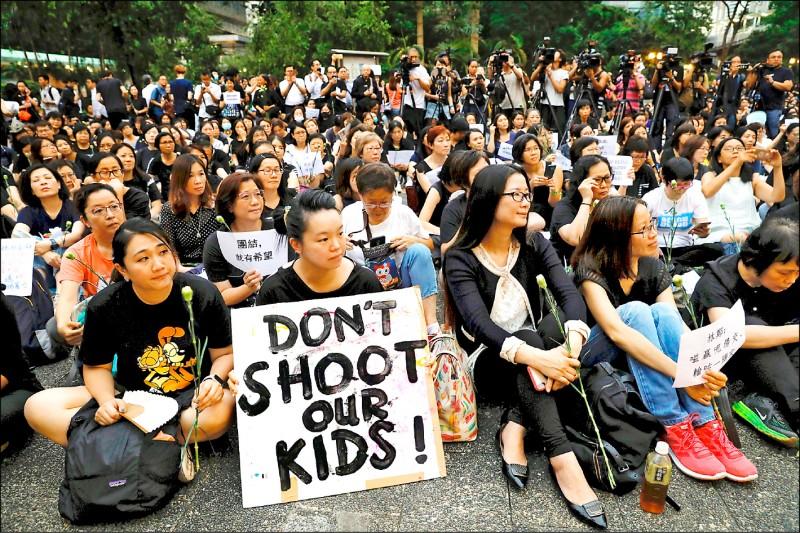 6千名香港家長14日晚間在香港中環的公園「遮打花園」,發起「香港媽媽反送中集氣大會」,為香港的年輕子女打氣,許多媽媽穿黑衣、持康乃馨參加,有人手持「別對我孩子開槍」、「撤案」等英文標語。(美聯社)