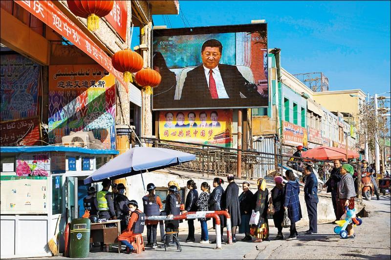 中國共產黨政府對人民的監控有增無減,尤其是對穆斯林占大宗的新疆維吾爾自治區。圖為位於新疆西南部的和田市集,兩年前即見入口設有檢查哨,民眾在播放中國國家主席習近平影像的大螢幕下排隊受檢。(美聯社檔案照)
