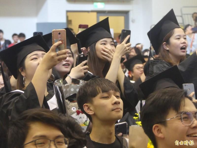 小英總統親臨金大畢業典禮,畢業生有的尖叫,有的趕快拿起手機拍照留下珍貴的一刻。(記者吳正庭攝)