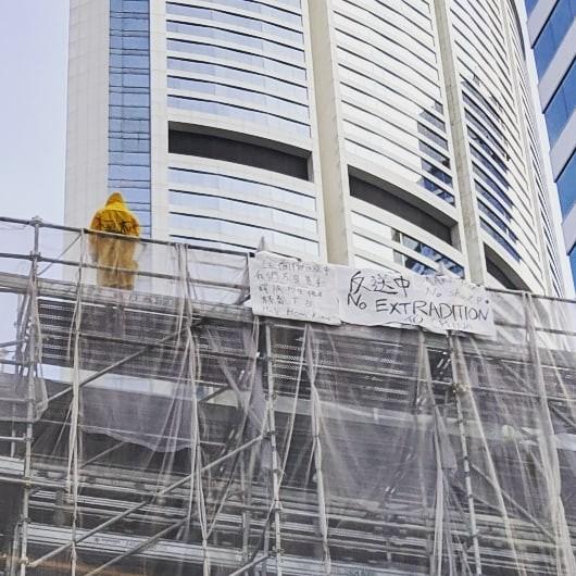 香港一名黃衣男子爬上金鐘太古廣場高處平台,掛出反送中標語。(圖擷取自rogerli_lfhk@IG)