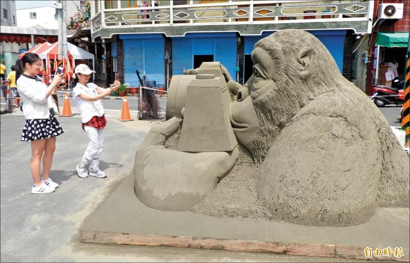 誰拍誰啊?「猴塞雷」沙雕作品,吸引遊客和沙雕互動拍照。 (記者楊金城攝)