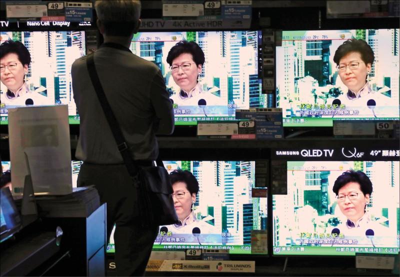一名香港民眾透過街頭的電視牆,觀看林鄭的記者會。(美聯社)