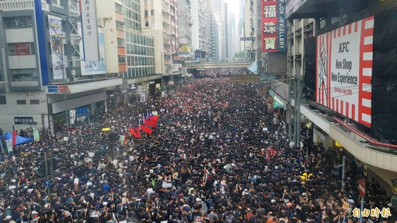 16日香港反送中大遊行滿滿穿著黑衣的人潮,據說人潮比9日遊行更多。畫面中還可見到整排中華民國國旗。(記者簡惠茹攝)