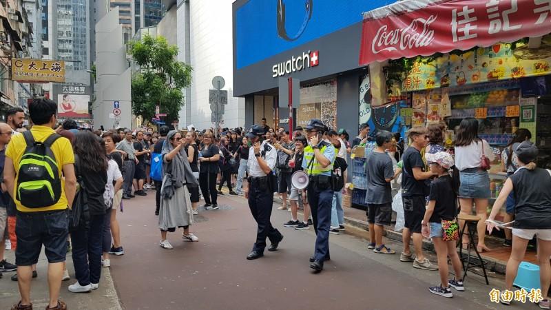 有民眾對警察拿鈴做收妖狀喊shame。(記者簡惠茹攝)