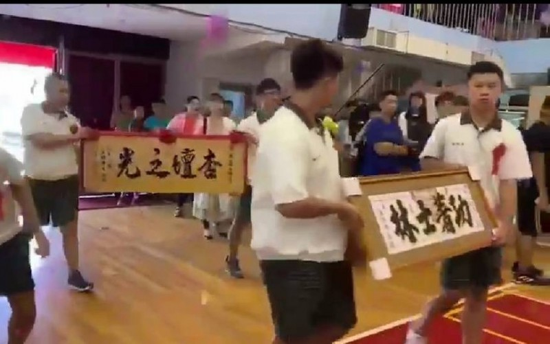 四位國中畢業生在畢業典禮代表把兩幅送給班導師的謝師匾額送進會場。(記者王俊忠翻攝)
