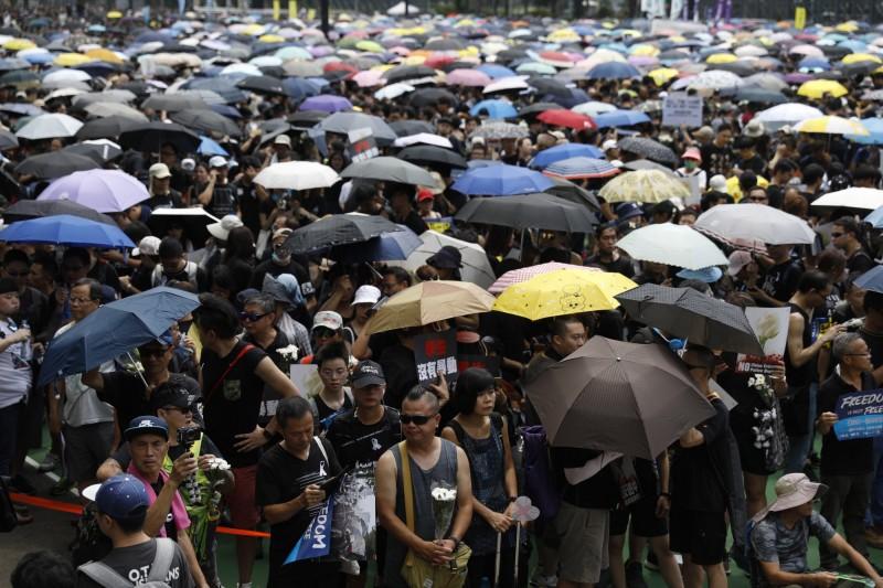 大批香港民眾身穿黑衣繫上白絲,手持帶前往集結點維多利亞公園。(歐新社)