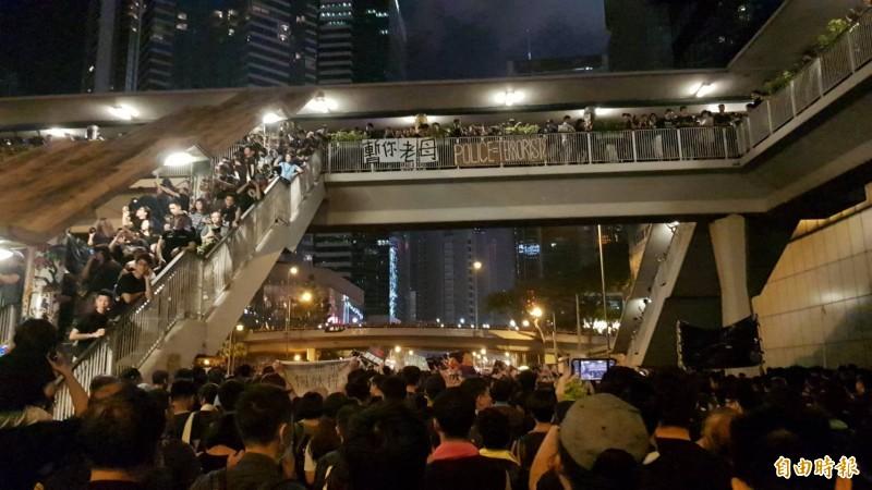 16日香港反送中大遊行入夜後人潮依舊擠滿整條街道,天橋上也站滿示威群眾呼應。(記者簡惠茹攝)
