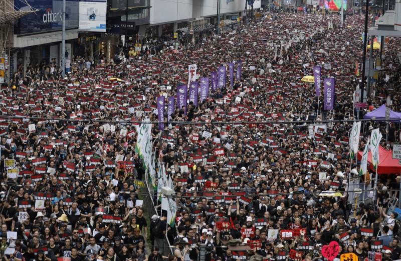 大批民眾穿上黑衣,一邊高呼「撤回」,一邊朝立法會進軍。(美聯社)