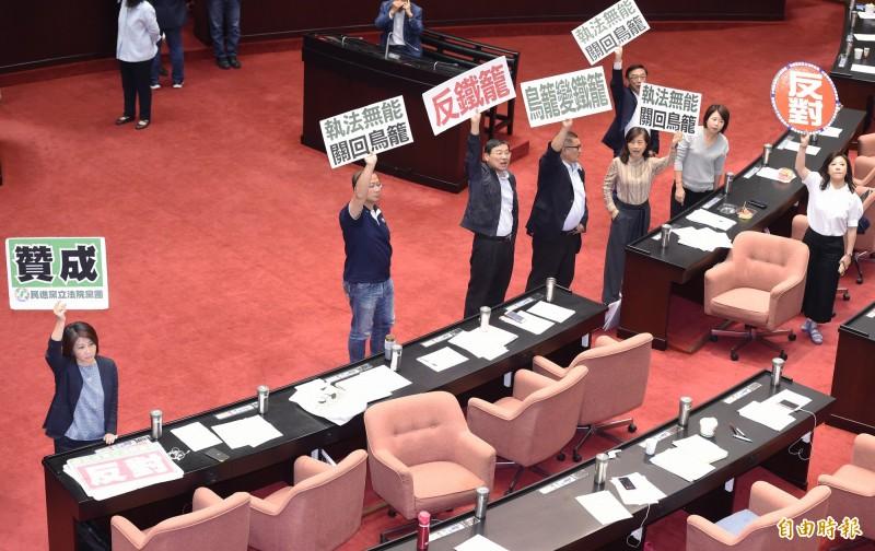 立法院17日召開第9屆第7會期臨時會,朝野黨團針對「公民投票法」修法進行協商,並對是否延長開會時間進行表決,國民黨立委高舉標語反對修惡公投法。(記者廖振輝攝)