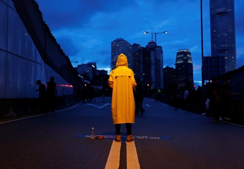 一名抗議者穿著黃色雨衣向日前身亡的「黃衣人」致敬。(路透)
