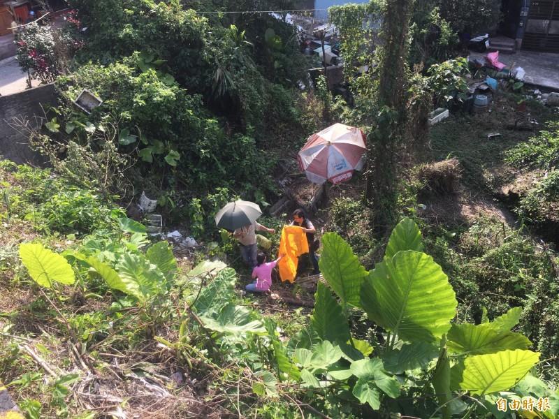 83歲李老翁今天午後被家人發現陳屍在住處前溝渠內,身體僵硬多時,李的媳婦、家人替他蓋上功德布,哭成一團,自責不已。(記者林嘉東攝)