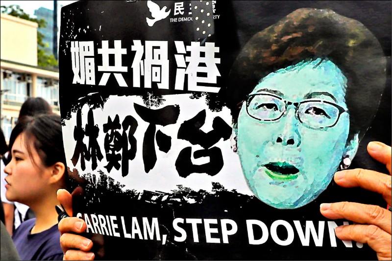 香港民眾十七日聚集在香港立法會外持續抗爭,一名抗議者手持印有特首林鄭月娥肖像的標語。(美聯社)