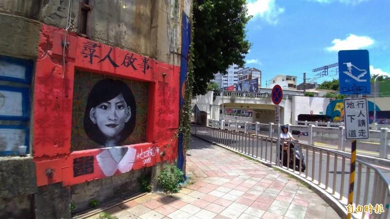 南市東區四維地下道附近的民族路旁牆面被畫上望之驚悚的大紅框女性人頭照塗鴉圖。(記者王俊忠攝)