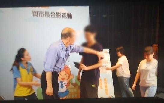 高雄市長韓國瑜19日與模範生及市長獎畢業生合照,遭到一名國中應屆畢業的男模範生當面表示「你選總統很可笑」。韓國瑜當下伸手將同學撥開。(記者洪定宏翻攝)