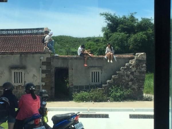 遊客任意攀爬民宅圍牆,侵犯私人產權。(民眾提供)