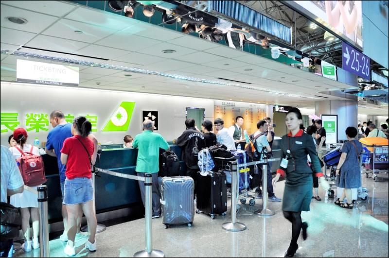 長榮空服突襲式罷工,機場地勤人員與旅客一一協調轉搭飛機航班事宜。(記者周敏鴻攝)