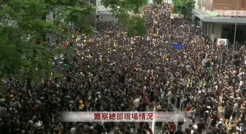 21日港民發起不合作運動,持續癱瘓香港金鐘、灣仔一帶的交通及政府服務,圖為香港警察總部遭群眾包圍。(擷取自《香港電台》直播)