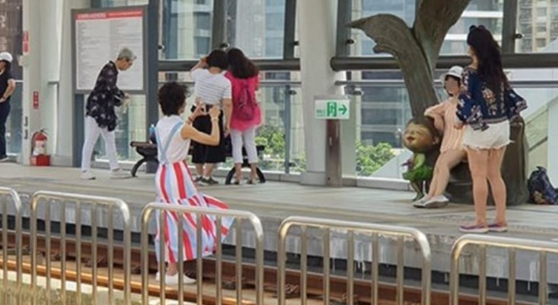 有遊客闖入淡海輕軌月台軌道區拍照取景,被網友抨擊行為不當。(圖擷取自細說淡水臉書社團)