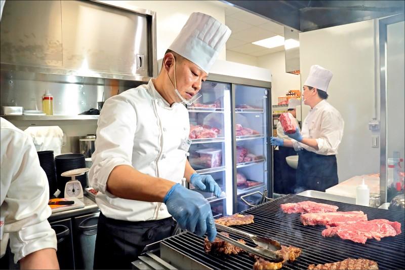主廚豪邁切開牛肉,將短暫醃過的肉塊上火爐。(記者陳宇睿/攝影)