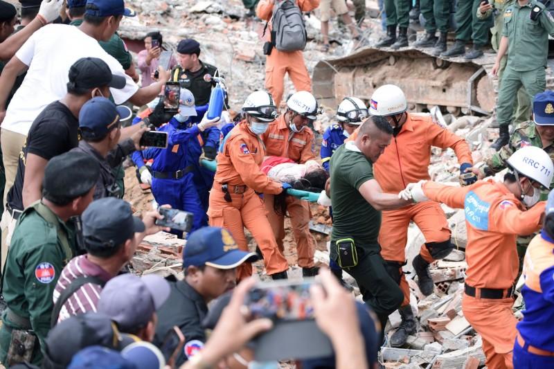 救援團隊從倒塌的建築中救出一名傷患。(路透)