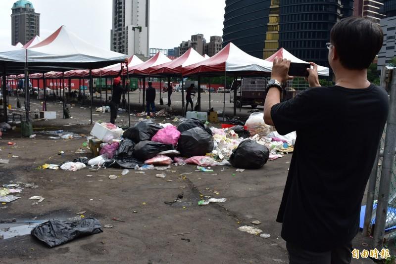 中市文資處的處長李智富,忙著拍攝造勢會場的垃圾。(記者張瑞楨攝)