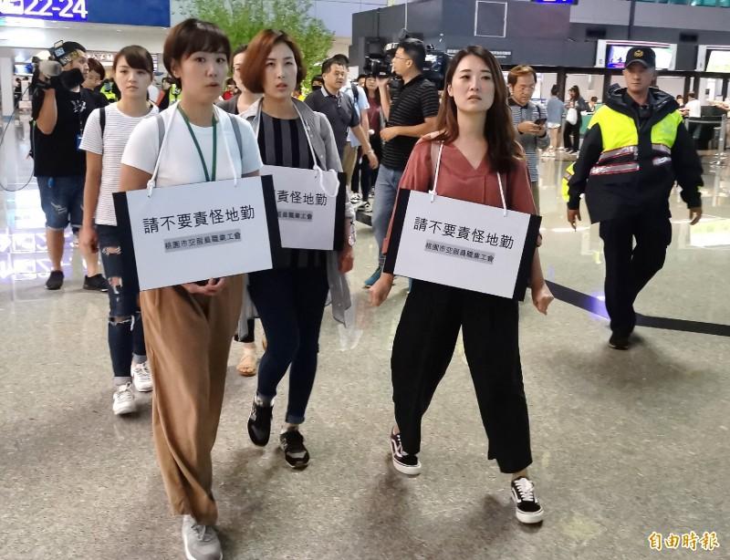 桃園職工罷工行動今天「轉戰」桃園機場,並在脖子掛着「請不要責怪地勤」的標語牌,她們說,爭取勞工權益的過程造成地勤、旅客的不便,深感抱歉。(記者姚介修攝)
