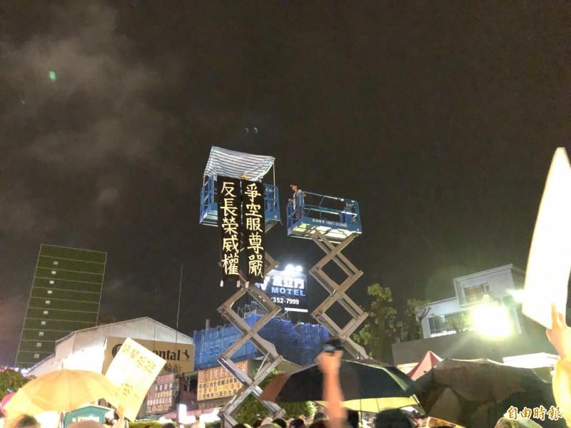 工會會員代表胡曉萱,在晚會結束前,發表了高空抗爭宣言,隨即爬上一旁約三層樓高的升降平台,表示自即刻起,將持續待在這個平台上,直到罷工結束。(記者魏瑾筠攝)