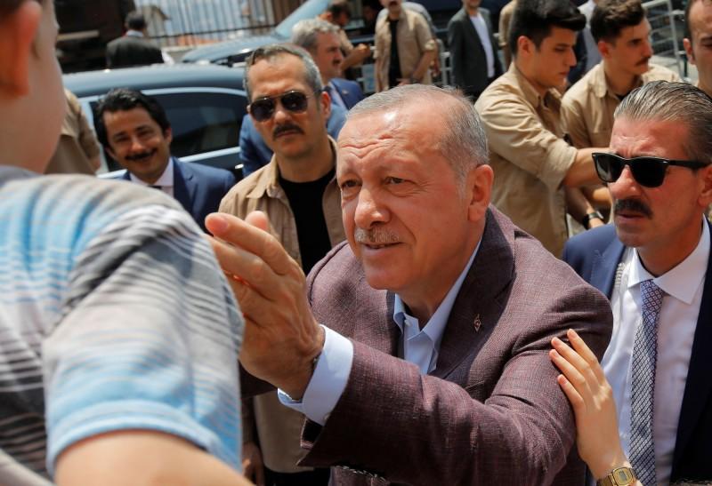 土耳其總統艾多根23日前往投票時,與支持者寒暄。(路透)