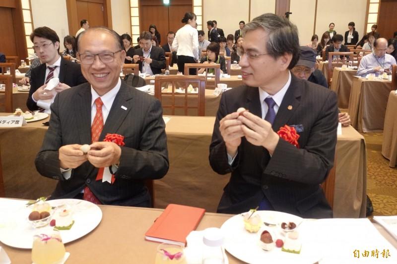 上銀董事長卓永財(左)連兩年領軍到日本行銷台灣頂級生鮮荔枝,24日行銷記者會上與台貿中心東京事務所主任的陳英顯(右)一起大啖荔枝。(記者林翠儀攝)