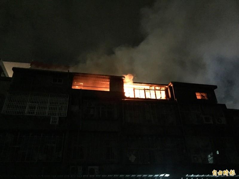 房屋後面的火勢猛烈。(記者邱書昱攝)