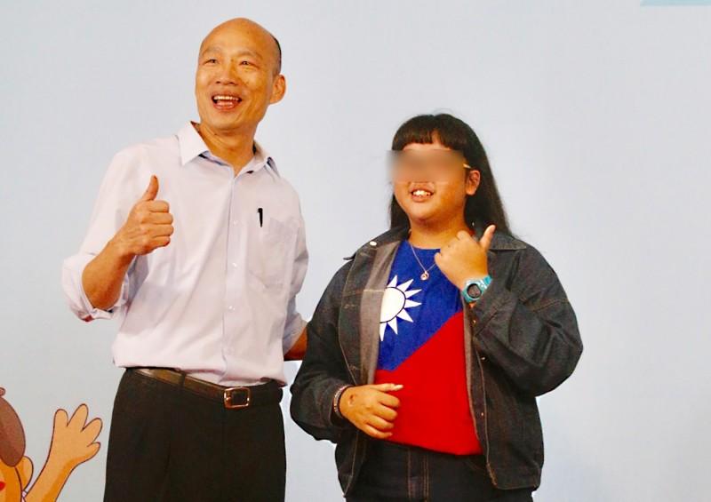 高雄市長韓國瑜(左)24日下午出席在左營新莊高中舉行的與模範生及優秀畢業生合影活動,有學生穿上國旗T恤出席。(中央社)