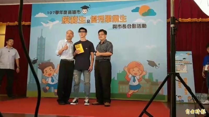 一名高雄中學畢業生(中)拿著心理叢書「為什麼愛說謊」由雄中校長謝文斌(右)陪同與韓國瑜(左)合影。(記者方志賢攝)