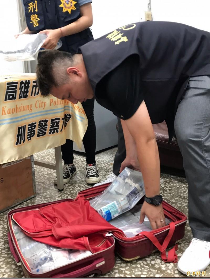 高市警掃黑緝槍查獲「洗錢」現金1880萬,估計不法滙兌近5億元,動用行李箱和點鈔機計算。(記者黃良傑攝)