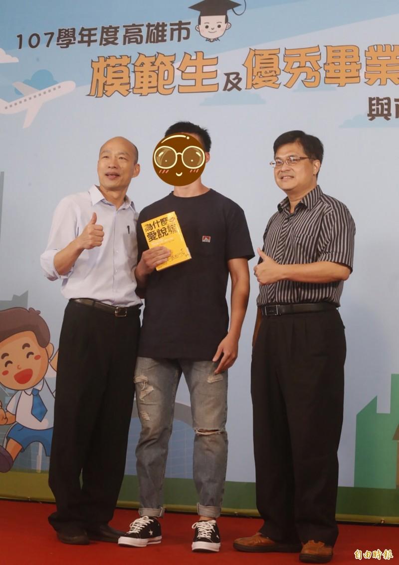 一名高雄中學畢業生(中)拿著心理叢書「為什麼愛說謊」由雄中校長謝文斌(右)陪同與高雄市長韓國瑜(左)合影。(記者張忠義攝)