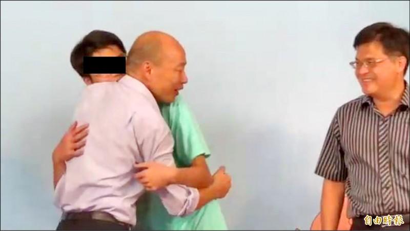 雄中畢業生穿趙天麟造勢T恤擁抱韓國瑜。(記者黃旭磊攝)