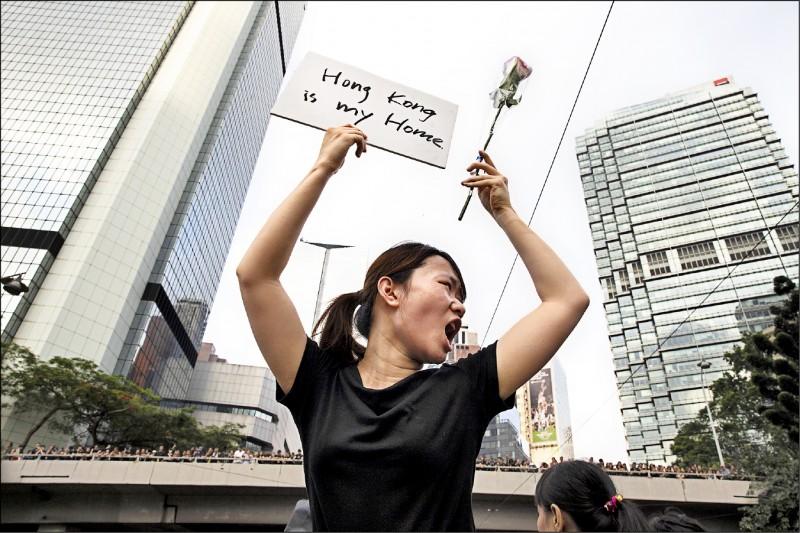 香港「反送中」抗爭期間,一名女子手持鮮花及寫有「香港是我家」的標語。(彭博)