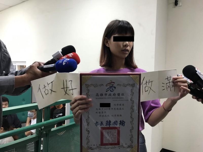 模範畢業生與市長韓國瑜合影嗆聲再進化!25日上午一名女學生將「做好做滿」字條藏在模範生獎狀下合影。(記者黃旭磊翻攝)