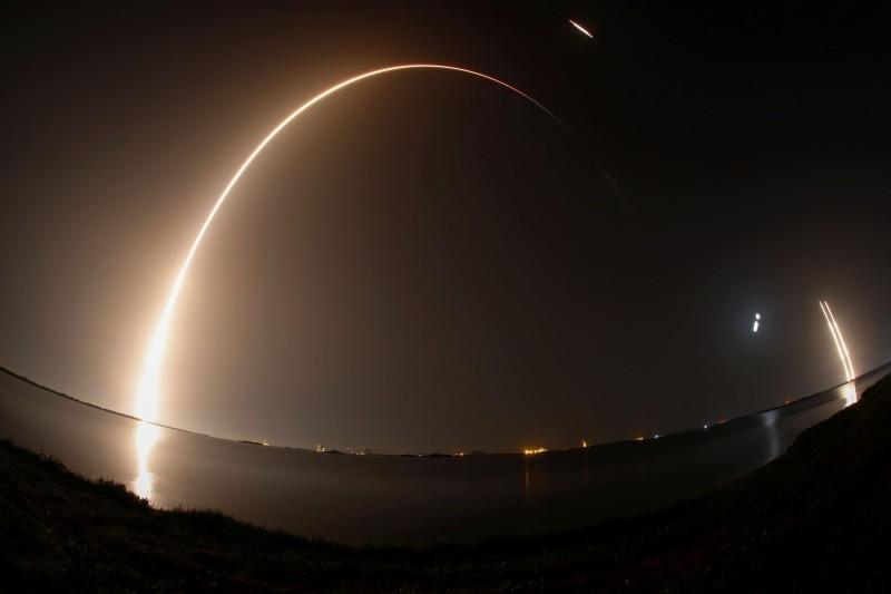 獵鷹重型火箭在夜空中劃出一道美麗弧線,遠方為側推進器回收。(路透)