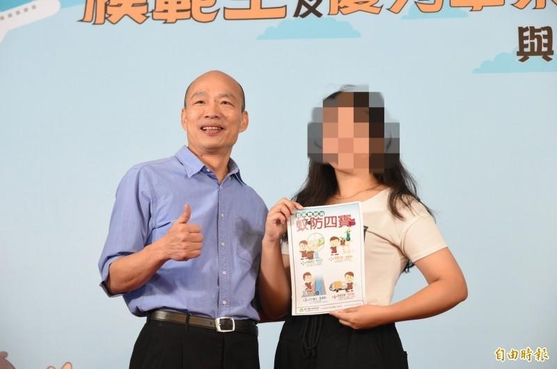 中華藝校陳姓畢業生則拿出登革熱防治文宣「防蚊四寶」,要韓國瑜做好防疫工作。(記者張忠義攝)