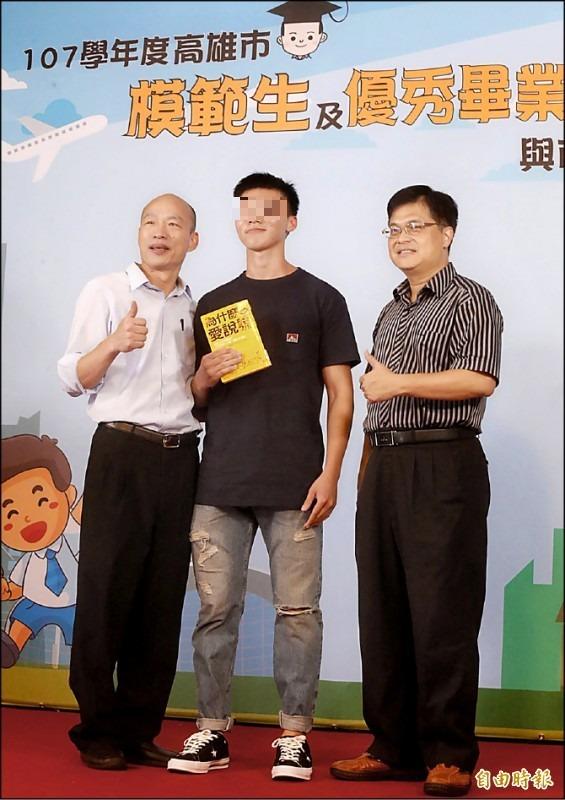 高雄市長韓國瑜(左)昨與模範學生及優秀畢業生合影,一名高雄中學畢業生(中)拿著心理叢書「為什麼愛說謊」與韓國瑜合影,嘲諷意味十足。(記者張忠義攝)